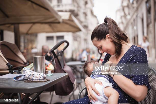 young mother breastfeeding her baby boy in public place - breastfeeding stock pictures, royalty-free photos & images