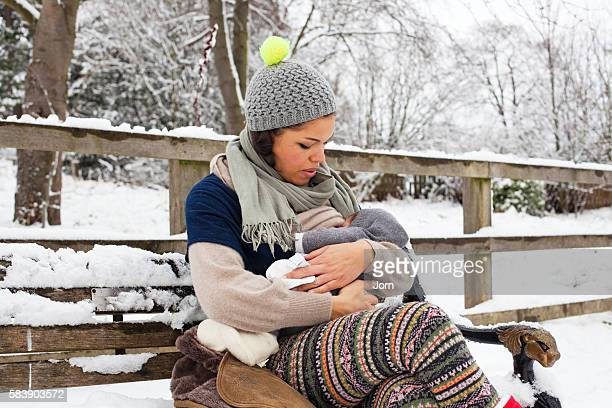 Young mother breastfeeding her baby (2-5 months) on park bench in winter