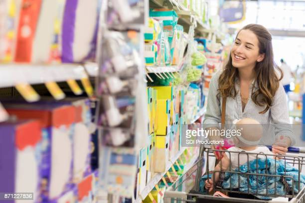 Young mother browses down baby aisle in supermarket