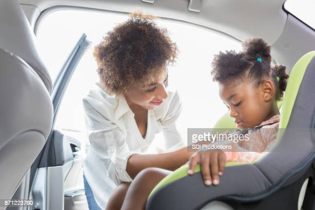 young mother buckles preschooler into car seat - family driving stock photos and pictures