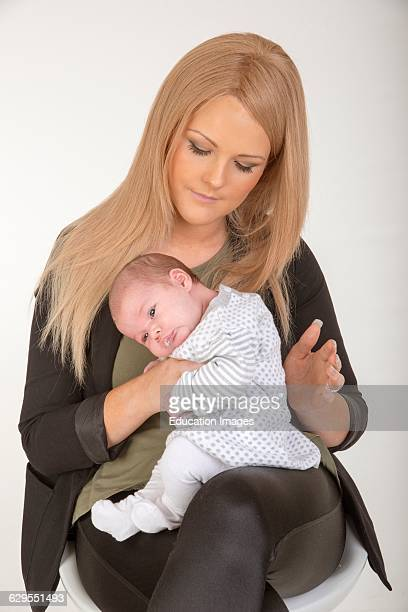 Young mother burping her new baby after breast feeding