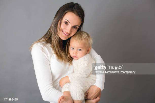 young mother, caressing her newborn baby boy, holding him in her arms and smiling from happiness - chest kissing stock pictures, royalty-free photos & images