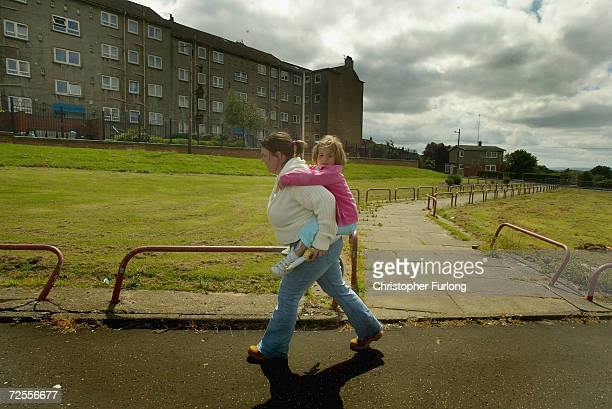 A young mother carries her child from school in the Barlanark area June 16 2004 of Glasgow Scotland The Barlanark area has been identified in a...