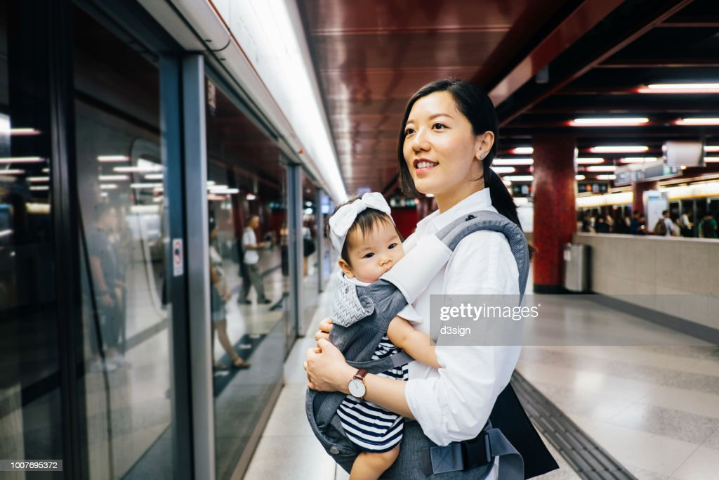 Young mother carrying cute baby girl waiting for subway in subway station : Stock Photo