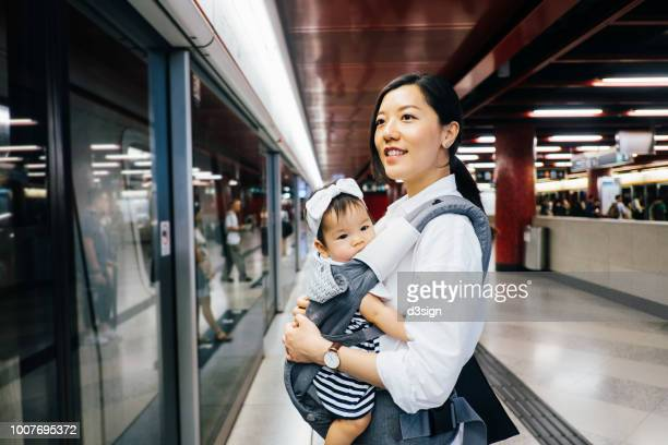 young mother carrying cute baby girl waiting for subway in subway station - homemaker stock pictures, royalty-free photos & images