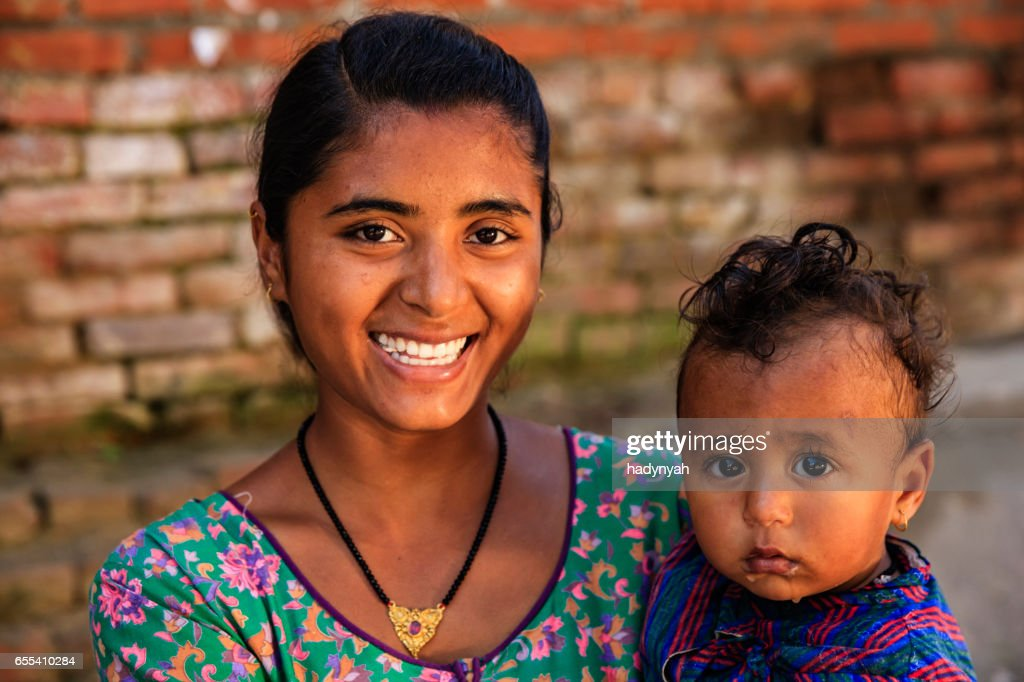 Young mother carrying her baby, Bhaktapur, Nepal : Stock Photo