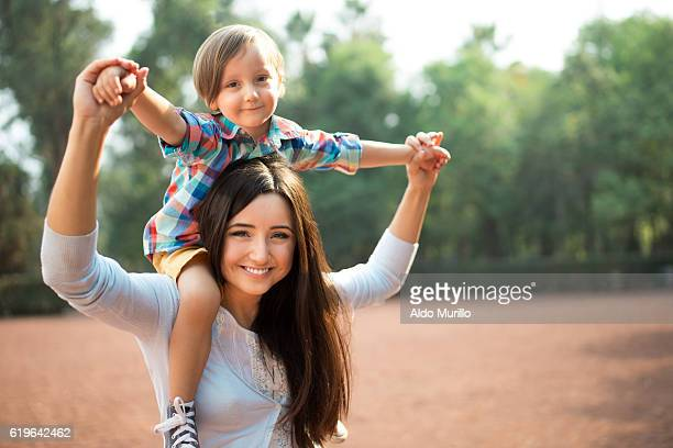 young mother carrying son on shoulders and holding hands - mexican mom stock photos and pictures