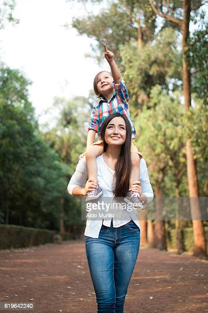 young mother carrying son on shoulders and looking away - mexican mom stock photos and pictures