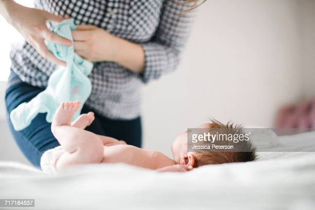 Young mother changing diaper to baby girl (0-1 months)