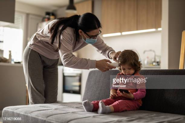 young mother checking temperature of her daughter at home during coronavirus pandemic - infrared thermometer stock pictures, royalty-free photos & images