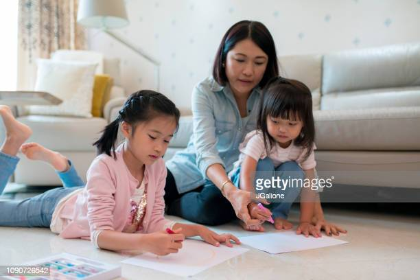 Young mother colouring with her children