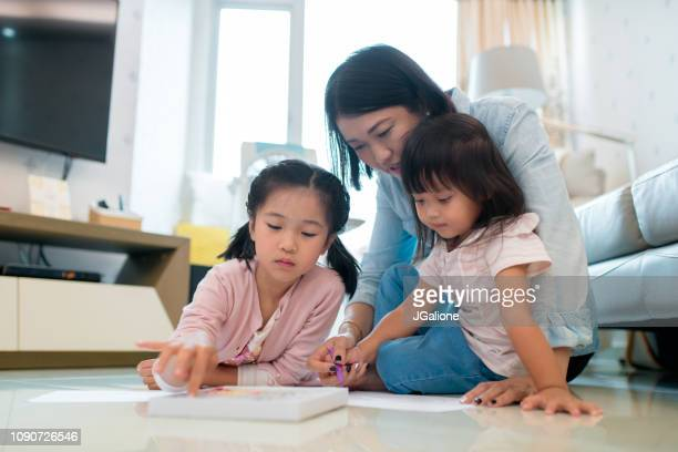young mother colouring with her children - family with two children stock pictures, royalty-free photos & images