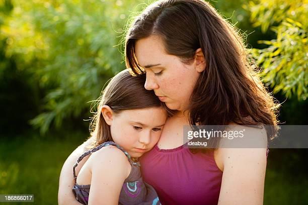 Joven madre con su hija pequeña reconfortante y sala de estar al aire libre