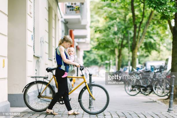 young mother commuting with her baby through the city - central berlin stock pictures, royalty-free photos & images