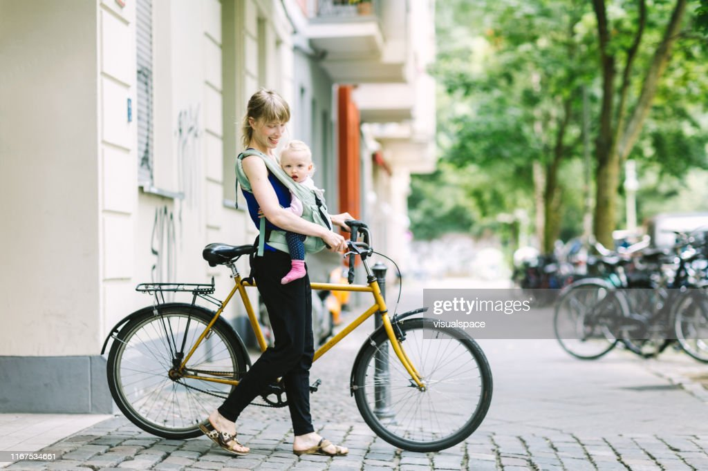 若い母親は、街を通って彼女の赤ちゃんと通勤 : ストックフォト