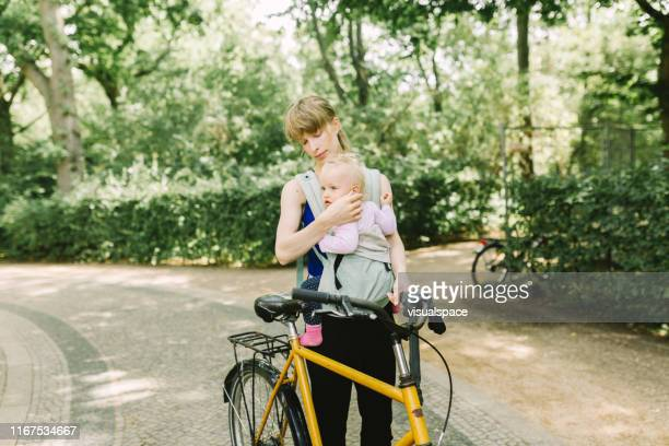 公園を通って赤ちゃんと通勤する若い母親 - プレンツラウアーベルグ ストックフォトと画像