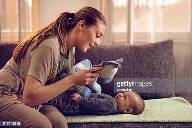 Junge Mutter trösten Ihr Baby weint mit einem Spielzeug.