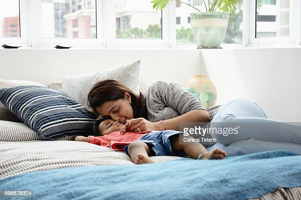 Young mother cudding her sleeping toddler on a bed
