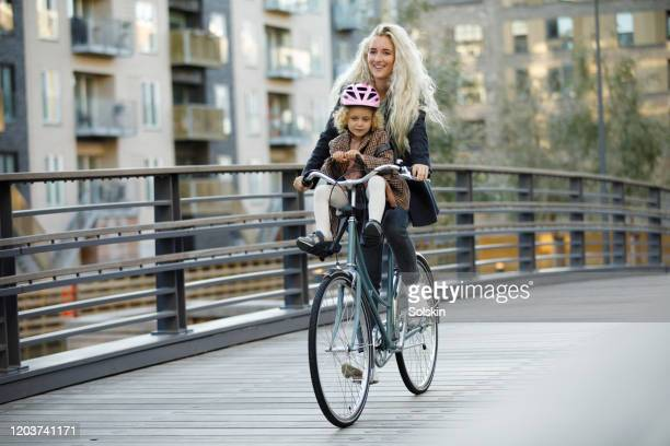 young mother cycling with daughter sitting on her bicycle - copenhagen stock pictures, royalty-free photos & images