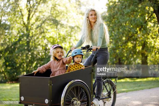 young mother cycling with two children in electric cargo bicycle - sunday stock pictures, royalty-free photos & images