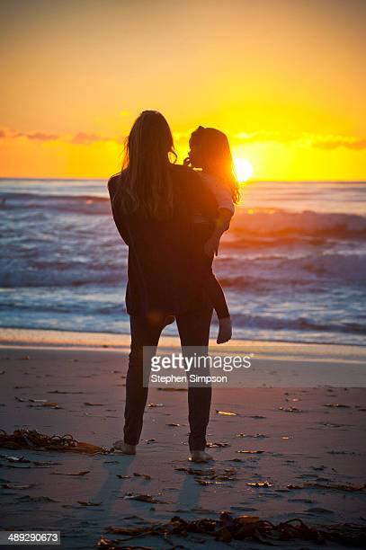 young mother & daughter watching the sunset