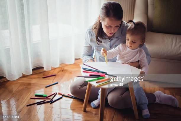 Young mother drawing with her son