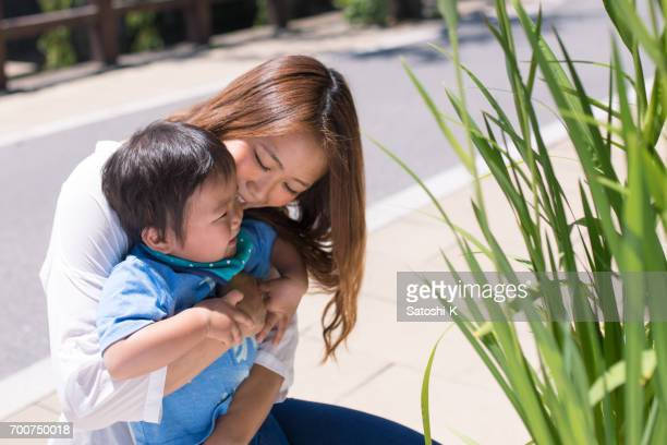 Young mother embracing baby on street
