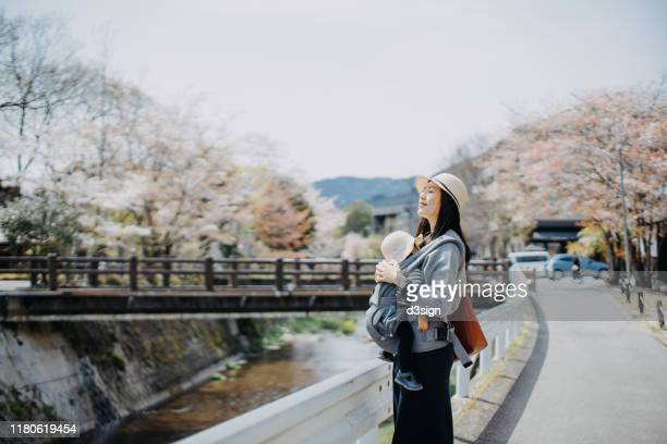 young mother embracing cute little daughter enjoying a spring day in the nature against beautiful cherry blossom - 息を止める ストックフォトと画像
