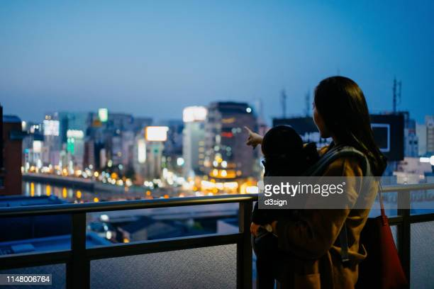 young mother embracing little daughter enjoying the beautiful city night view from the balcony - 福岡県 ストックフォトと画像