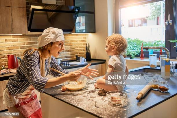 young mother enjoying cooking in the company of her baby - sugar baby imagens e fotografias de stock