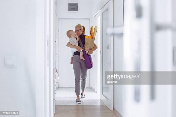Aufrufen junge Mutter zu Hause um ihr Baby und Lebensmittel-Tasche