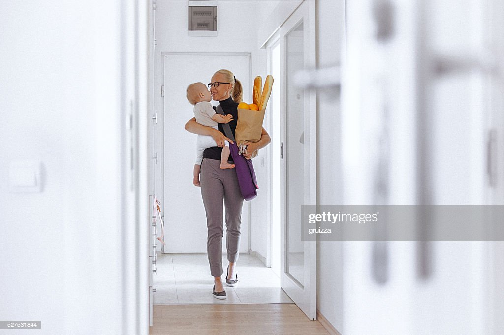 Young mother enters home, carrying her baby and grocery bag : Stock Photo