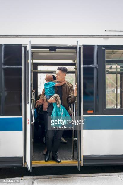 Young mother father and infant exiting city bus