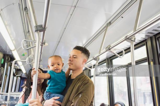Young mother father and infant riding city bus