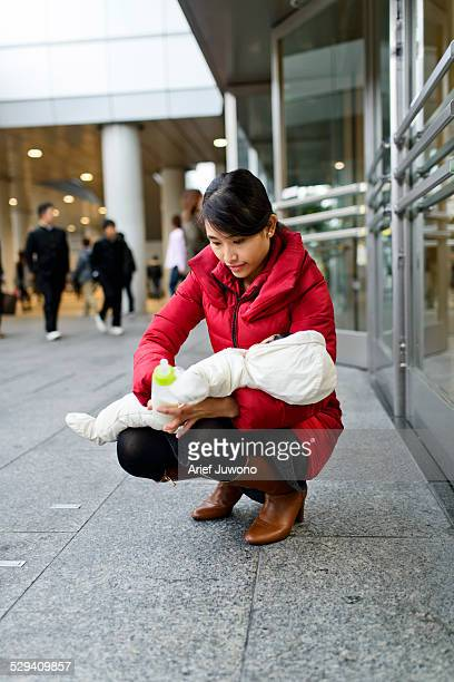 young mother feeding milk the baby outdoors - japanese breastfeeding stock pictures, royalty-free photos & images