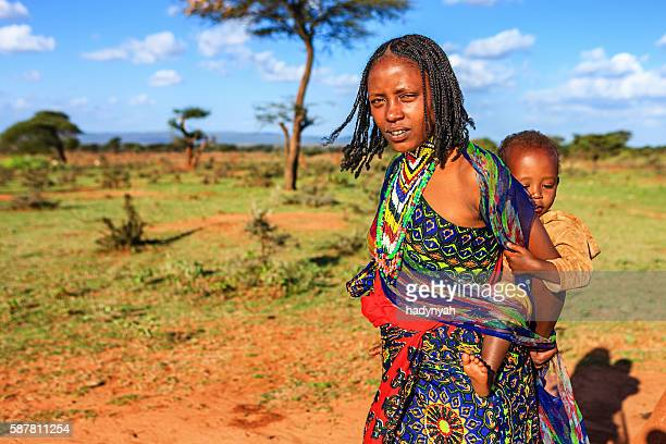 young mother  from borana tribe carrying her baby, ethiopia, africa - african tribal culture stock pictures, royalty-free photos & images