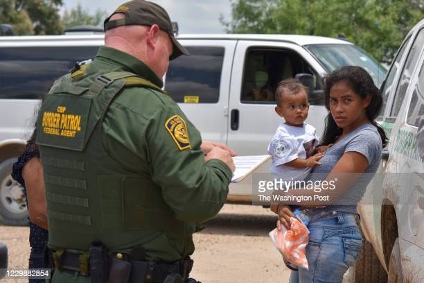 Young mother from Honduras and her 1-year-old child are detained by United States Border Patrol after rafting across the Rio Grande on the...