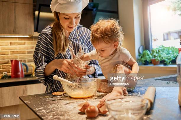 young mother getting assistance in cooking by her baby - sugar baby imagens e fotografias de stock