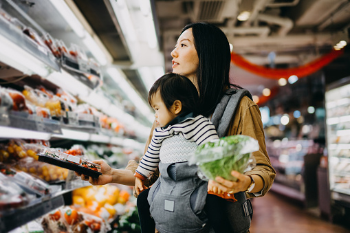 Young mother grocery shopping with baby girl in supermarket, shopping for fresh organic vegetables and fruits - gettyimageskorea