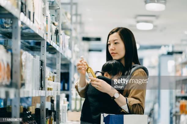 young mother grocery shopping with little daughter in a shop. she is holding a bottle of organic cooking oil and reading the nutrition label - 専業主婦 ストックフォトと画像