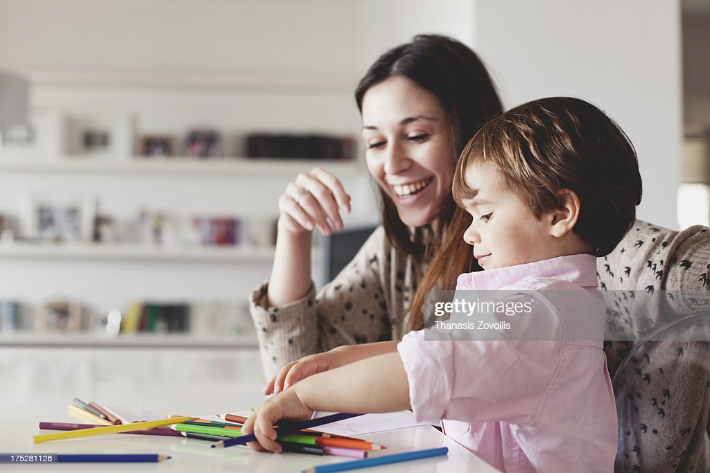 Young mother help her son with drawing : Stock Photo