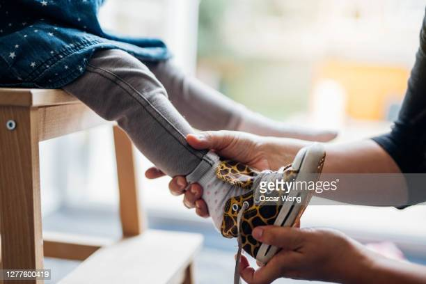 young mother helping daughter to put on shoes - education stock pictures, royalty-free photos & images