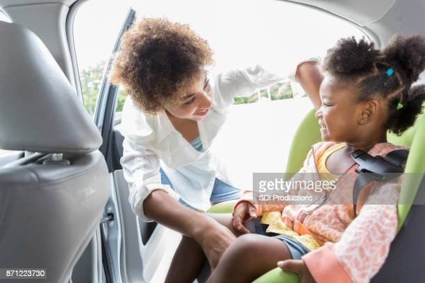 Young mother helps preschooler with seat belt