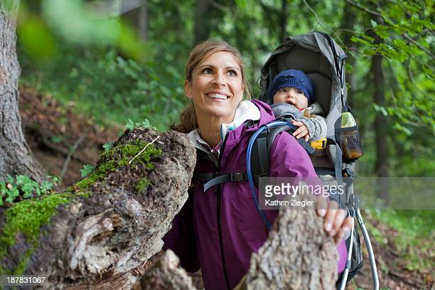 young mother hiking with girl in baby carrier