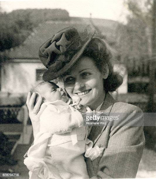 Young mother holding baby smiling, Switzerland October 1944