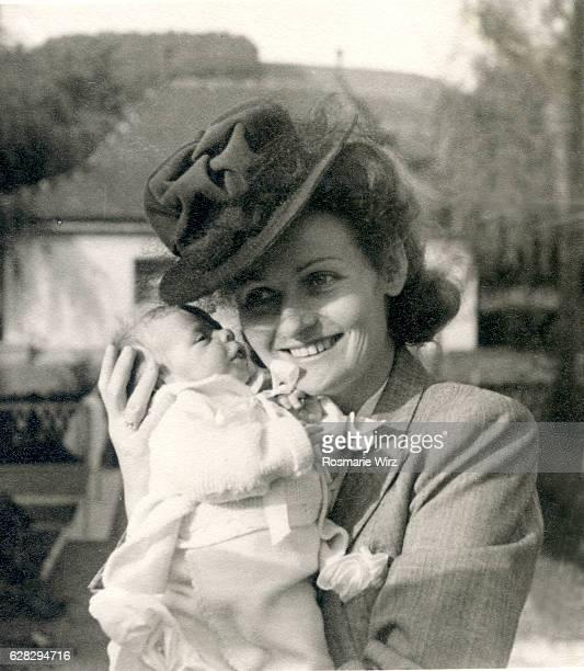 young mother holding baby smiling, switzerland october 1944 - archivmaterial stock-fotos und bilder