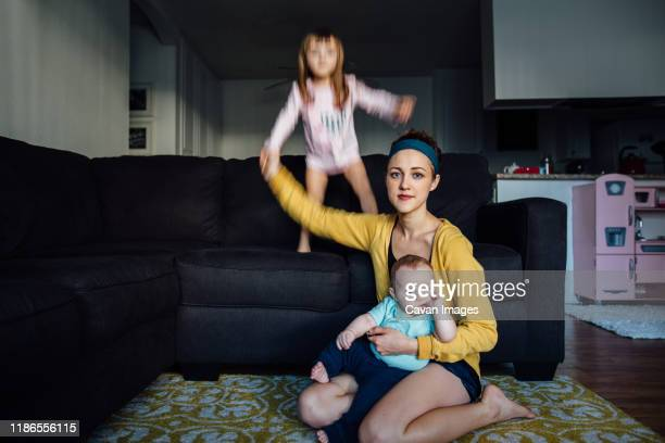 a young mother holding her baby while her toddler jumps on the couch - chaos stock-fotos und bilder