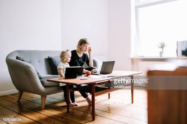 若い母親は、彼女の幼児が彼女のそばにいる間、ホームオフィスでビデオ通話を開催します - ワイドショット ストックフォトと画像