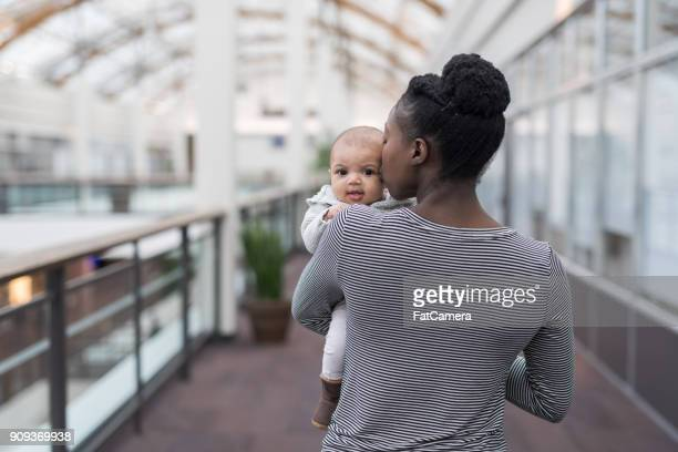 Young mother holds and kisses her baby daughter while out shopping