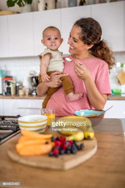 Young mother in a kitchen feeding a baby